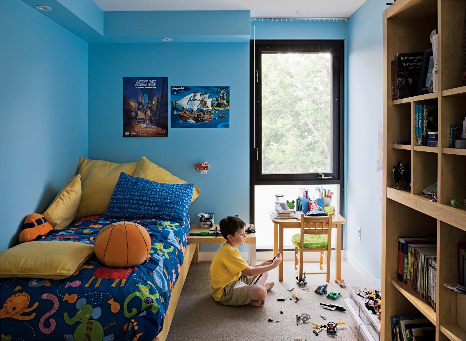 Kids, Bedroom, Boy, Pre-Teen, Desk, Bed, Night Stands, Chair, Carpet, Shelves, and Storage Griffin's room, which is exactly the same size as his brother's, gets good light from the backyard.  Kids Storage Bedroom Shelves Carpet Photos from Narrow Modernist Three-Story Home in Toronto
