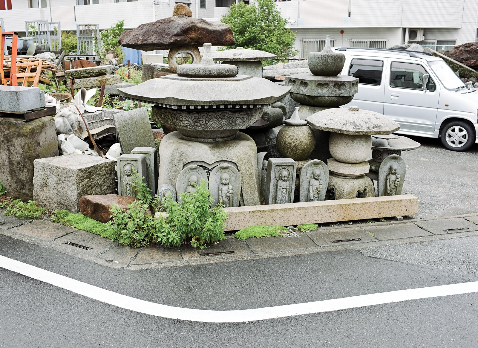 Local stonemasonry across the street.  Photo 2 of 14 in Small Box Home with Black Metal Facade in Japan
