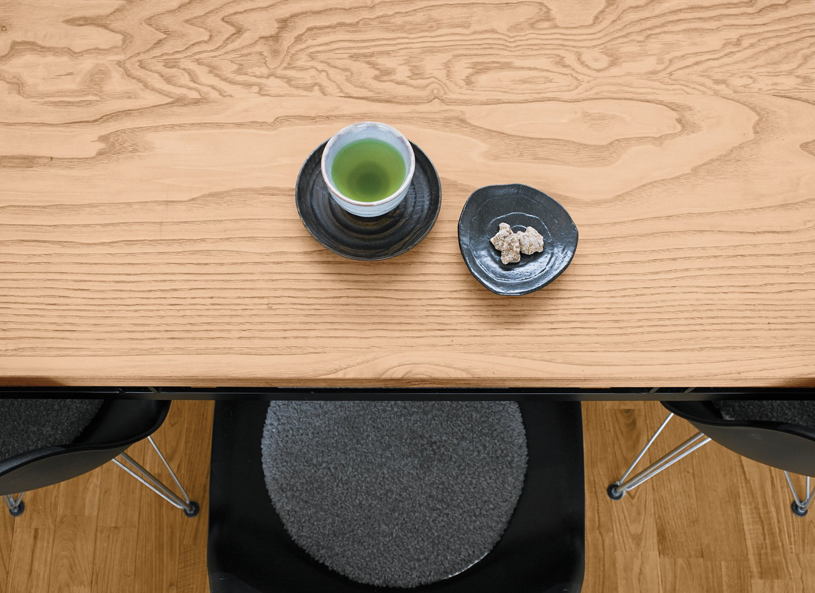 Dining Room, Table, Chair, and Medium Hardwood Floor Green tea and a sweet for a guest.  Green