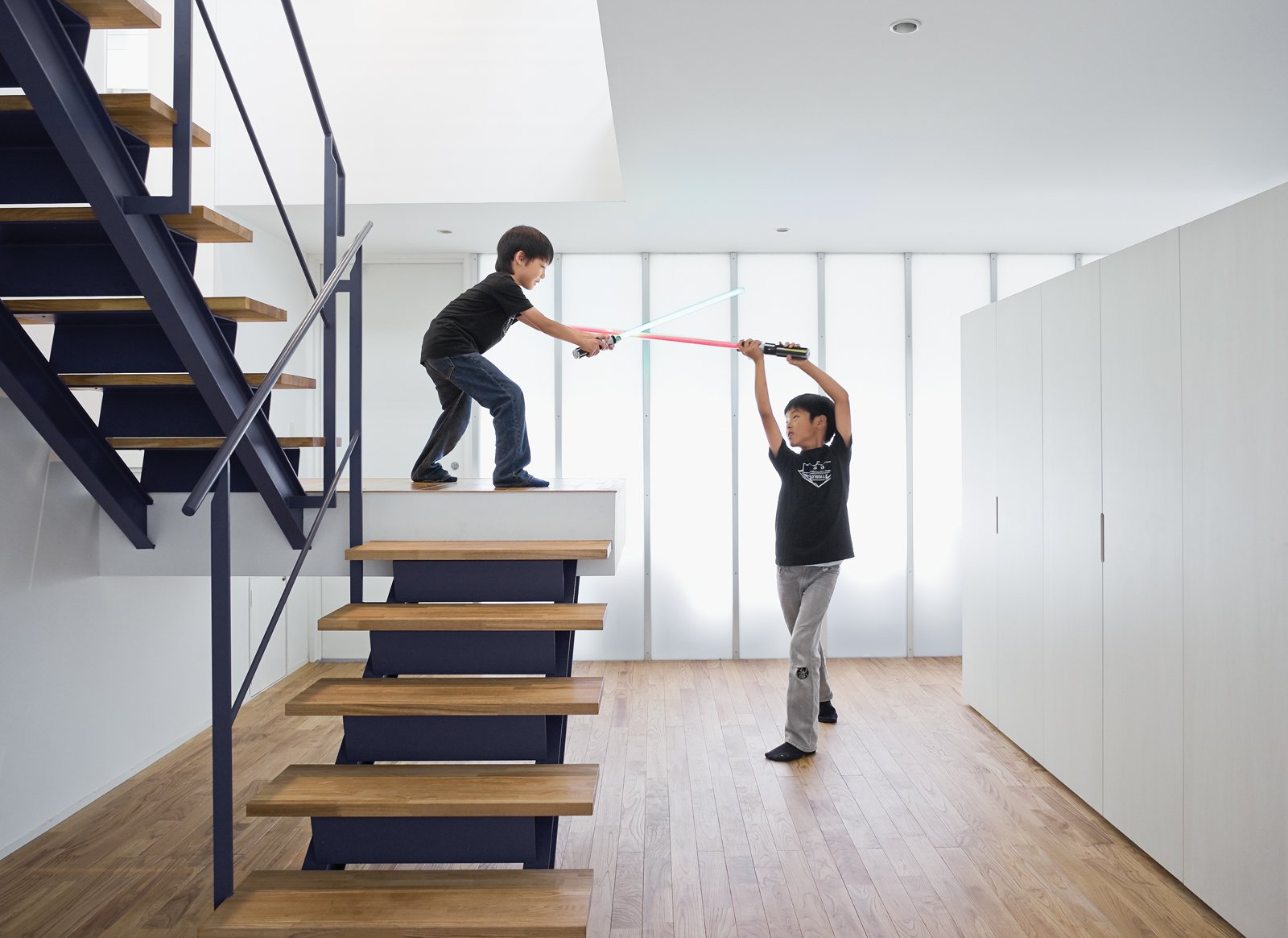 Staircase, Metal Railing, and Wood Tread The open-tread stair leading from the garage to the second-floor living room sets the stage for a Star Wars–style duel.  Photo 12 of 14 in Small Box Home with Black Metal Facade in Japan