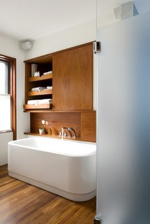 "The leftmost cabinet above the Duravit bathtub (equipped with KWC fixtures) occupies the space where a doorway once lead into the living room, creating unnecessary traffic from the home's public spaces through to the master bedroom.The new bathroom features a minimal palette of white and teak. ""It's able to hold up on boat decks so is good for a bathroom,"" Klug says. It also makes the heated floor that much nicer to walk on in the morning.  Photo by   Eric Roth"