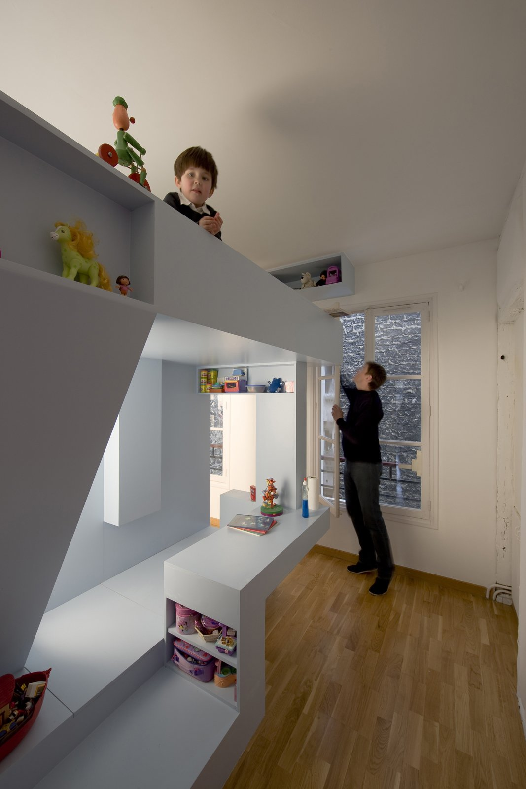 It's hard to be small and see the world from the eye level of adults' knees. In the children's bedroom, Eva's viewing perspective is reversed, and she observes her brother and parents from on high as she perches in her bed.  Photo 6 of 11 in Kids' Room Renovation