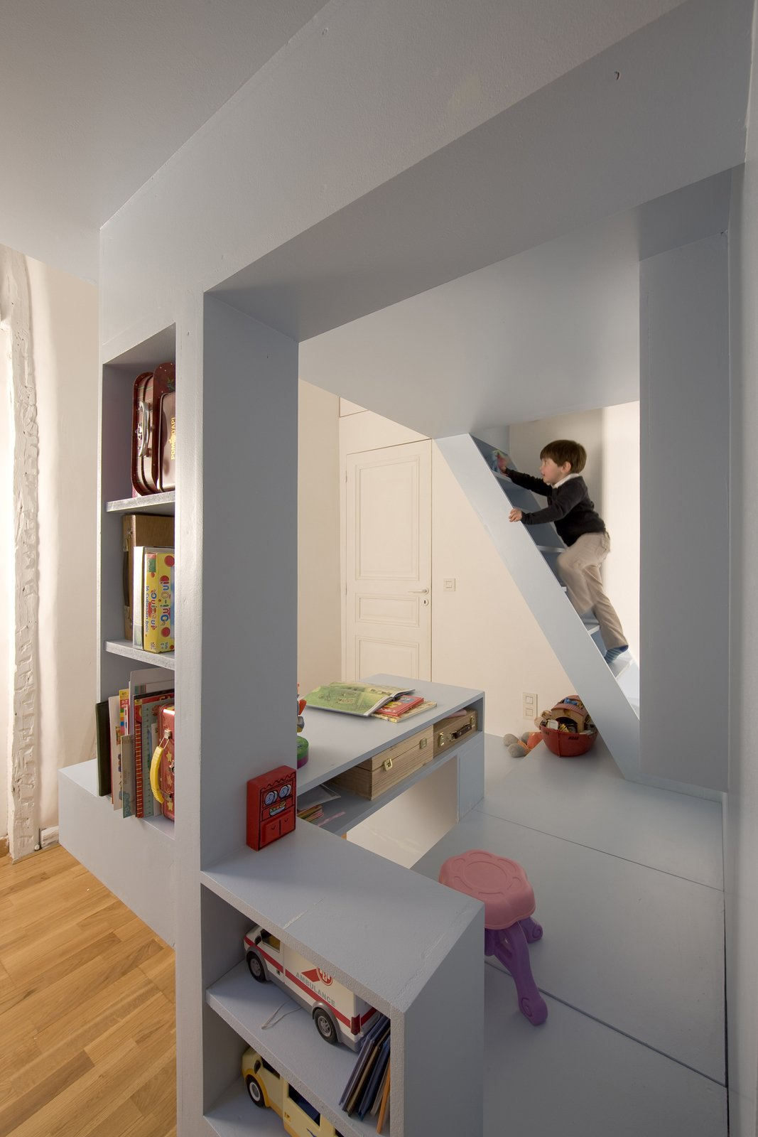 For additional storage, the floor of the partition (shown here beneath the pink stool) easily opens to reveal additional storage space below.  Photo 8 of 11 in Kids' Room Renovation