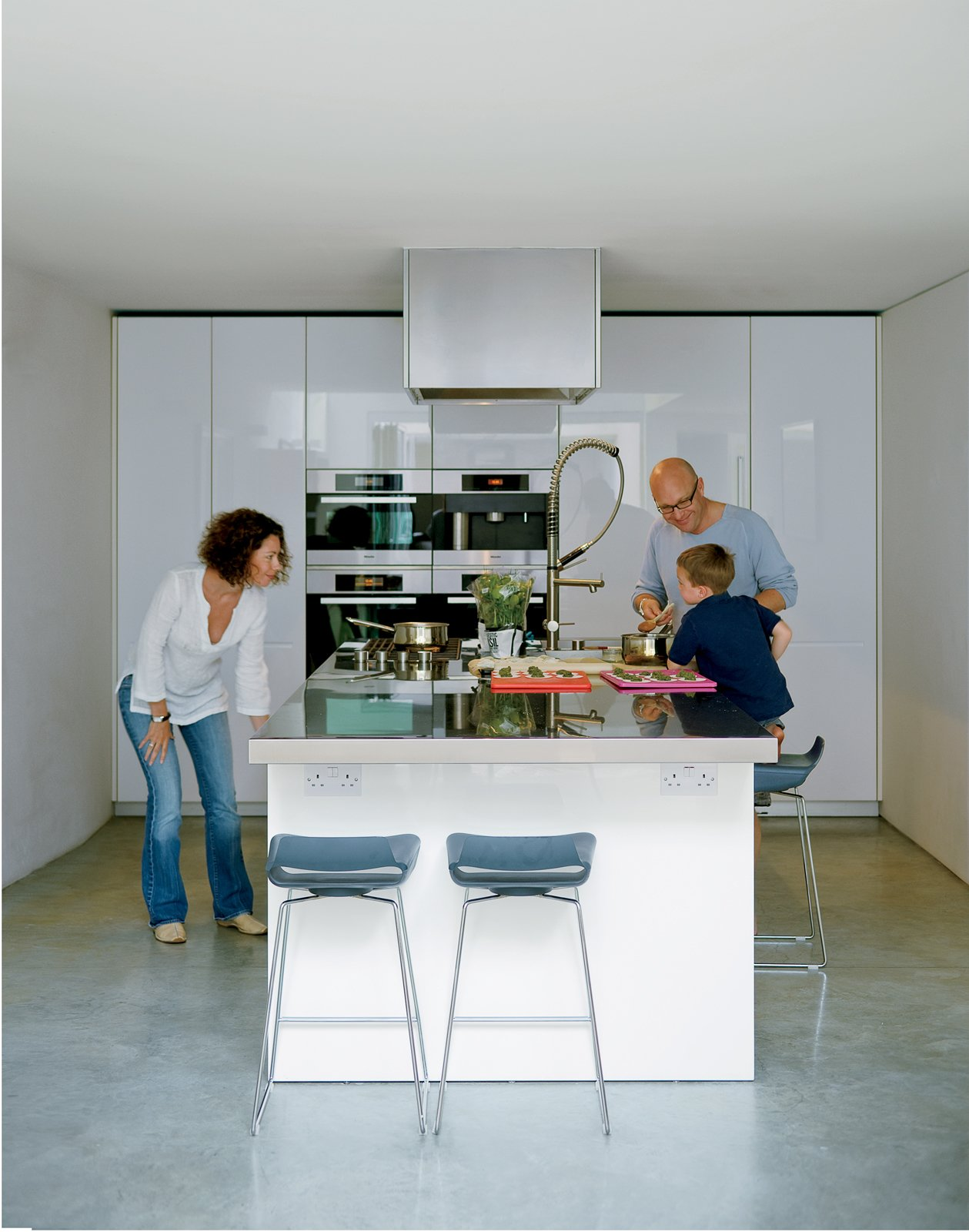 Kitchen, Wall Oven, and White Cabinet Bruce and Kirsty loved the idea of a kitchen island rather than traditional work surfaces around the walls. Bruce fancies himself a chef and hates to have his back to everyone when he's cooking. This island, from the Boffi LT line designed by Piero Lissoni, allows guests to gather around for impromptu sushi rolling or casual breakfasts.  Photo 5 of 10 in Composite Index