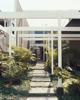 The Opdahl House, designed by Edward Killingsworth for Richard and Joyce Opdahl, is located on the island of Naples, in Long Beach, California, and the design responds to the constraints imposed by the compact site.Unlike the neighbors, whose  homes unflinchingly abut their property lines, Killingsworth set the Opdahl House 42 feet back from the street, dedicating half of the lot to a dramatic entryway that includes a carport, garden, and reflecting pool. The effect is one of entering a private sanctuary.