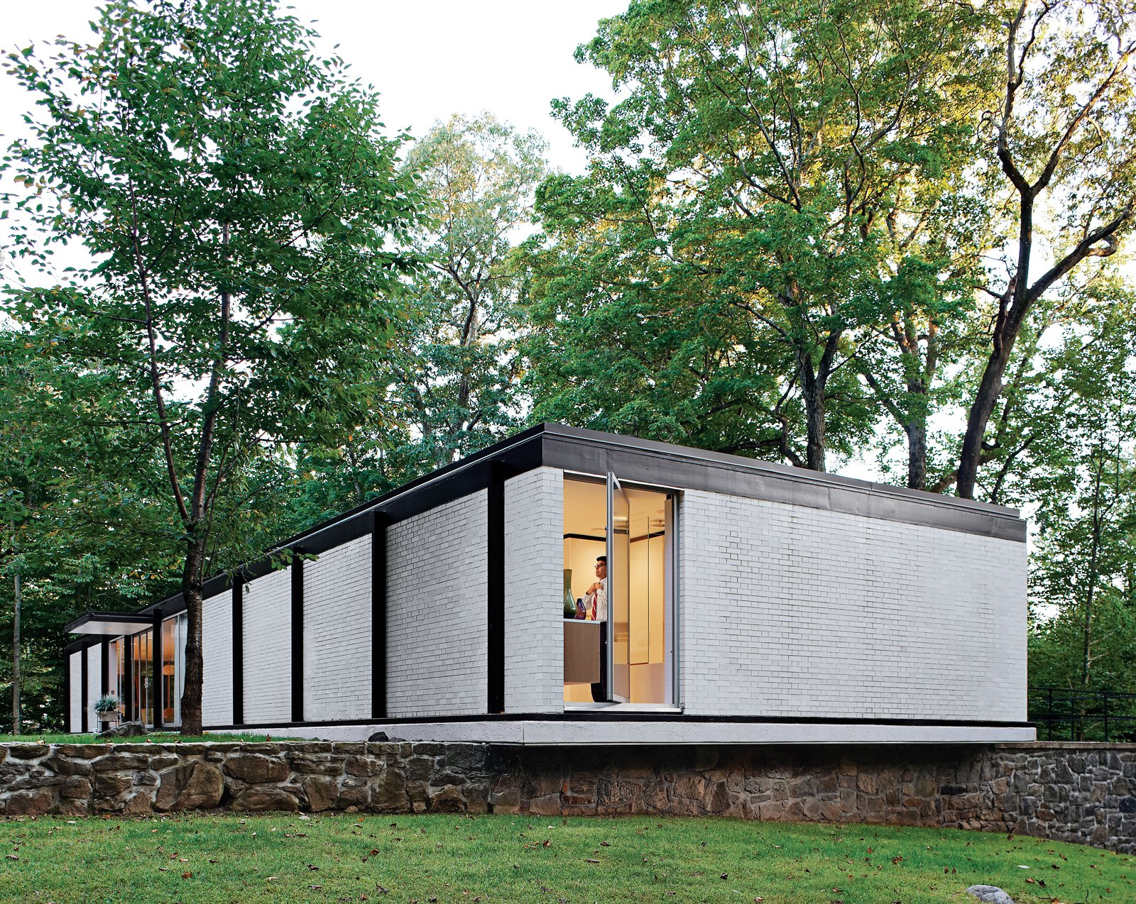 Exterior, Flat RoofLine, Mid-Century Building Type, House Building Type, and Brick Siding Material White brick exterior of Goddard and Mandolene's home post renovation.  Best Photos from Mod Men