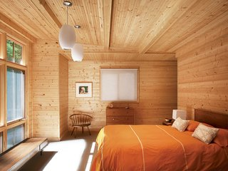 A tastefully spare selection of vintage pieces accents the warm knotty pine in the master bedroom. The orientation of the room maximizes the picture window that replaced the original garage door. Campbell designed a closet in an alcove behind the wall at the head of the bed.