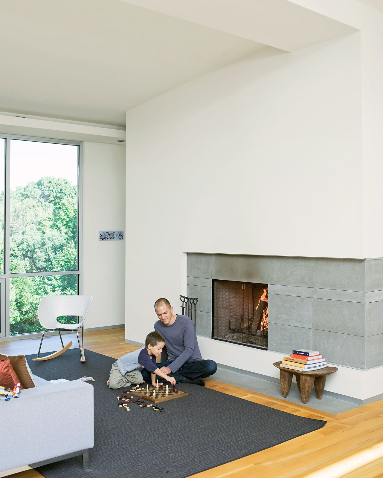 Living Room, Light Hardwood Floor, Standard Layout Fireplace, and Chair Christian and Jack play chess by the fireplace - the centerpiece of the living room and which the Arnolds use daily during the winter. The hearth is made of large slabs   of limestone, which Christian cut himself, intentionally leaving imperfections on the surface for texture. A studio8 couch and Vitra Tom Vac Rocker articulate the space.  Photo 4 of 7 in A Lot to Love