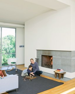 Christian and Jack play chess by the fireplace - the centerpiece of the living room and which the Arnolds use daily during the winter. The hearth is made of large slabs   of limestone, which Christian cut himself, intentionally leaving imperfections on the surface for texture. A studio8 couch and Vitra Tom Vac Rocker articulate the space.