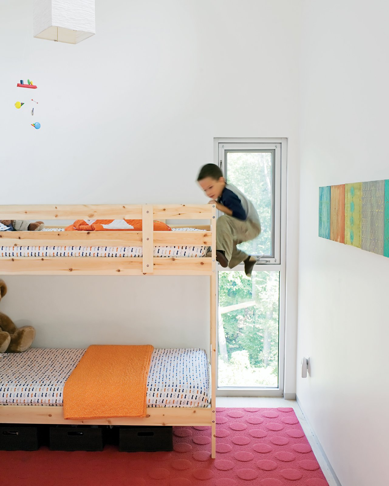Kids Room, Bedroom Room Type, and Bunks In the kids' room, Jack climbs the bunk bed he shares with his little brother, James. The paintings on the wall were done by their mom.  Photo 7 of 7 in A Lot to Love