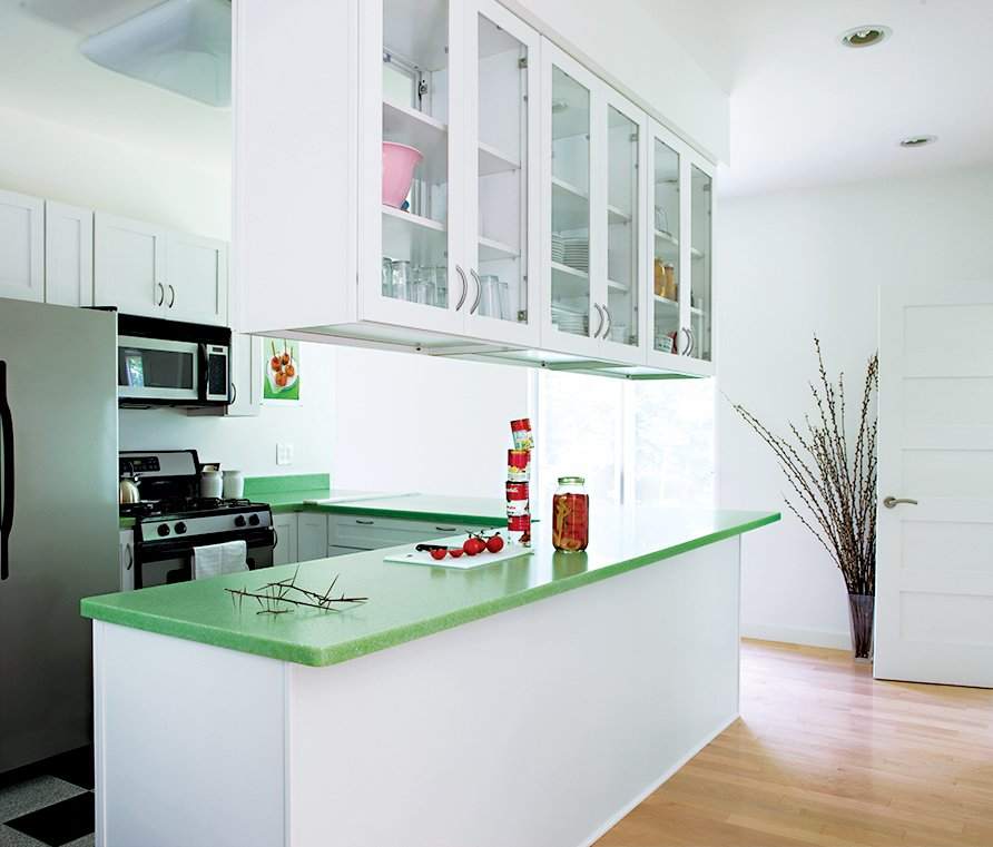 Kitchen, Light Hardwood Floor, White Cabinet, Quartzite Counter, Recessed Lighting, Refrigerator, Range, and Microwave A leaf-green countertop adds a splash of color to the kitchen.  How to Design with Green by Diana Budds from Bringing It All Back Home