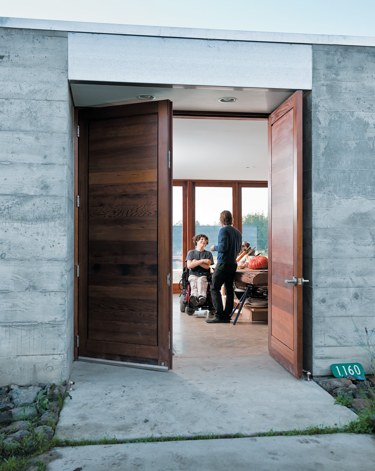 Doors, Wood, Swing Door Type, and Exterior The wide front door opens onto a wide central living space where the entire family—and a regular cast of visitors—spends much of their time.  Photo 10 of 11 in 10 Fantastically Sleek Foyer Designs from Fertile Grounds