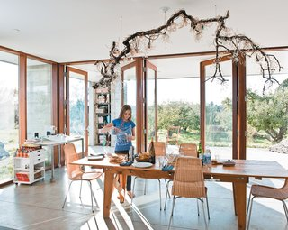 The dining room table sits at one end of the main room, with an open view onto the rows of trees that extend out from two sides of the house. Natasha sets the table underneath a suspended fixture made by her mother, Naomi, out of a salvaged branch, crystal pieces, and strung bulbs.