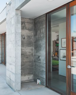 An outdoor shower is made from one complete concrete module—a visual demonstration of how the entire house was built.