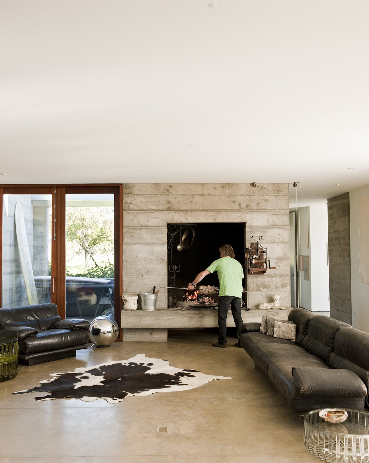 """Living Room, Standard Layout Fireplace, Concrete Floor, and Sofa The oversize hearth (of which there is an outdoor double) was part of the original design specifications. """"Ben said he wanted a fireplace big enough to cook a wild boar,"""" says Mark Anderson of Anderson and Anderson.  Photo 18 of 23 in Fertile Grounds"""
