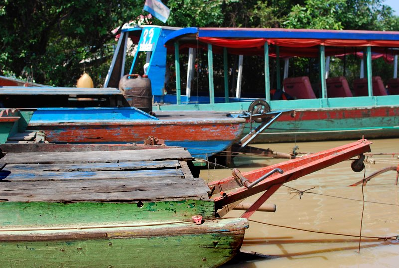 Several of the colorful wooden tourist boats lined up, also known as 'river taxis.'  Living on Water: Floating Villages by Tiffany Chu