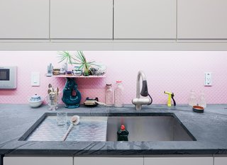 Painting this diamond-plate steel backsplash a charming pink color makes the material feel less cold and industrial.
