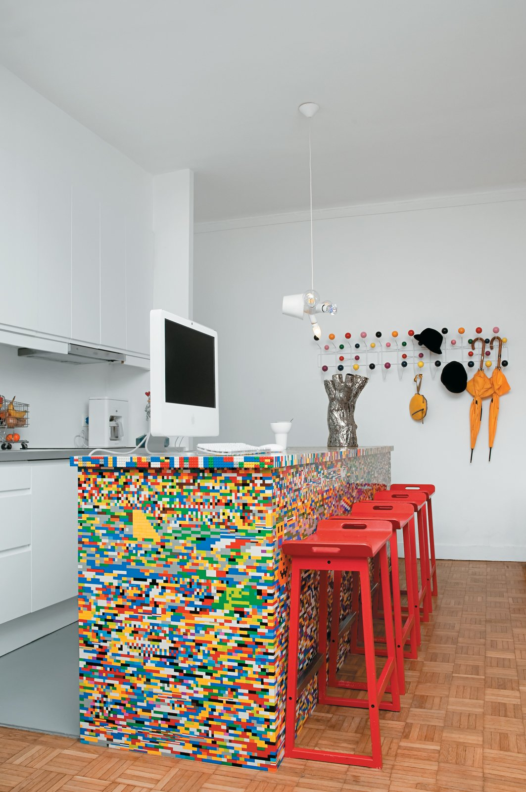 Kitchen and White Cabinet The idea for Simon Pillard and Philippe Rossetti's Lego kitchen in Paris sprouted five years ago, when Pillard put 500 blocks and a day's worth of work into building a Lego-legged chair. The designing duo—who create products together under the name Munchausen—recently gave the seat a colorful companion. They covered their kitchen island—a simple wooden block—with 20,000 Lego pieces.  Photo by Céline Clanet  Fantastic Modern Kitchen Islands by Brandi Andres from Lego Island
