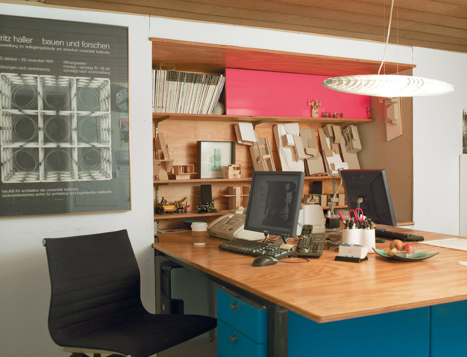 The architectural office below the living quarters is compact, with just enough space for shared workstations and a bookcase made of plywood and pink Plexiglas.  Photo 10 of 15 in How to Design with Pink from How Good Idea Studio Revamped a 1924 Clapboard House on a $62,000 Budget