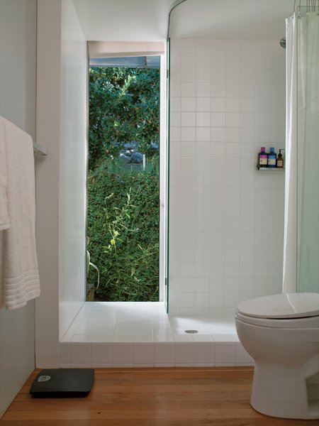 At $2.75 a square foot (which includes a designer discount), Molina and Turin could afford to extend matte white ceramic tiles from Dal-Tile beyond   the conventional shower boundaries to give the bathroom the look of   a brighter, more expansive space.