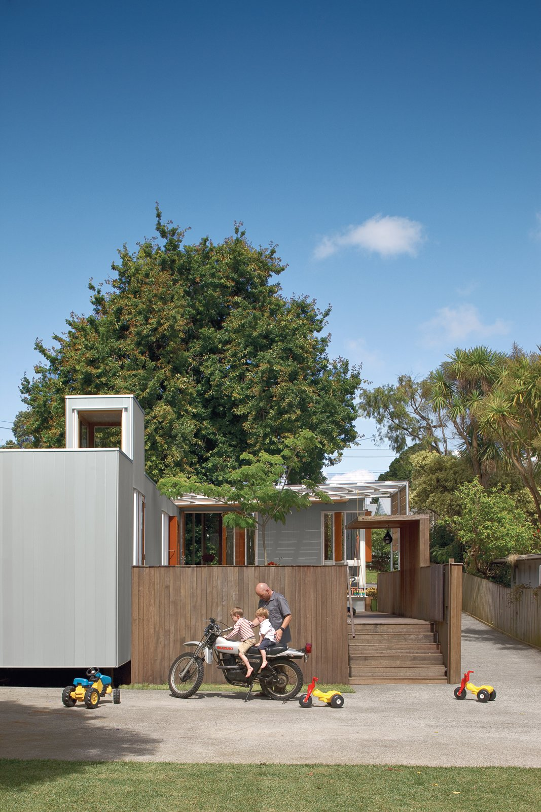 Exterior, House Building Type, and Wood Siding Material In the suburb on the mountain's lower slopes, Michael O'Sullivan and his sons Seamus and Finbar exchange motorcycle tips outside the compact, innovative home O'Sullivan designed.  Photo 3 of 11 in The Great Compression