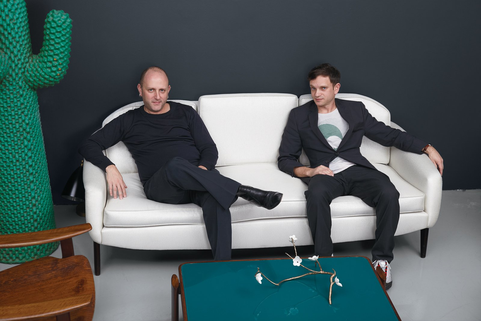 Owners Zesty Meyers and Evan Snyderman lounge on this Stella sofa from Sergio Rodrigues. Also shown, bronze branch by David Wiseman, and Cactus coat rack by Guido Drocco and Franco Mello.  Revival of the Fittest by Jordan Kushins