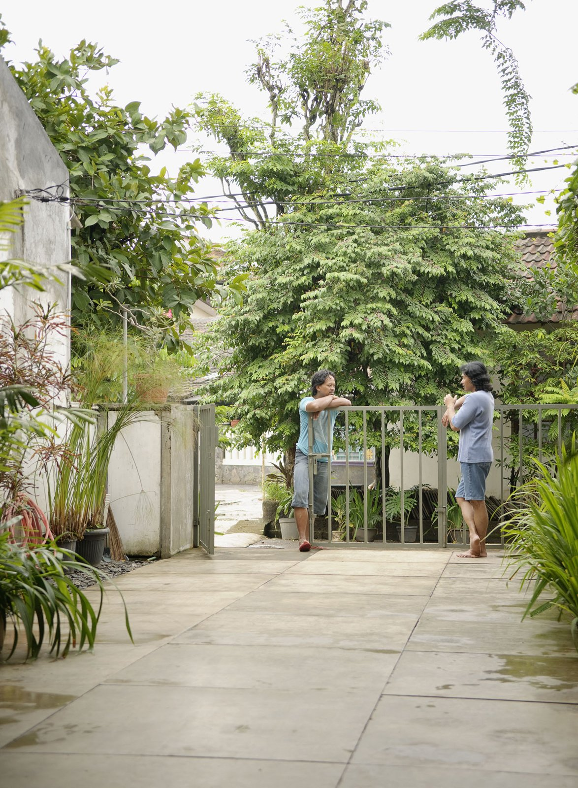 Wisnu and Sundari have a chat at the gate, which just barely keeps Jakarta's heavy vegetation at bay.  Photo 15 of 26 in Humid City, Cool Home