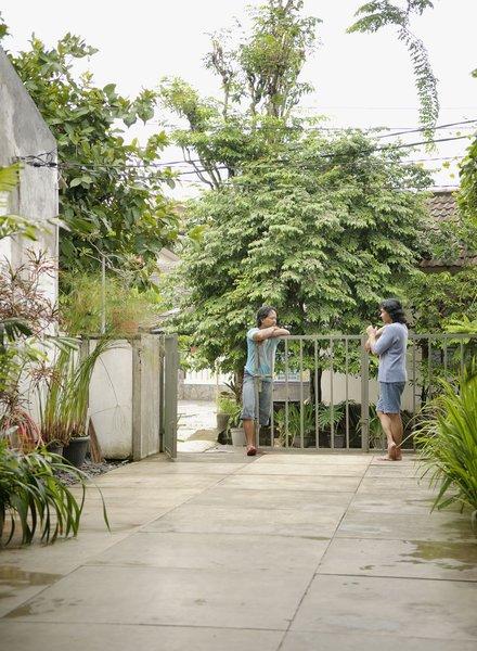 Wisnu and Sundari have a chat at the gate, which just barely keeps Jakarta's heavy vegetation at bay.