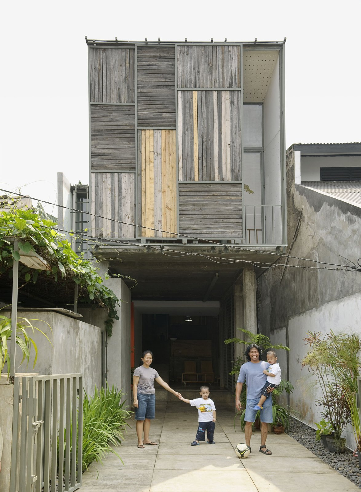 The family poses in the driveway out front of the house. The sliding panels on the facade allow a peek into the balcony just inside.  Photo 18 of 26 in Humid City, Cool Home