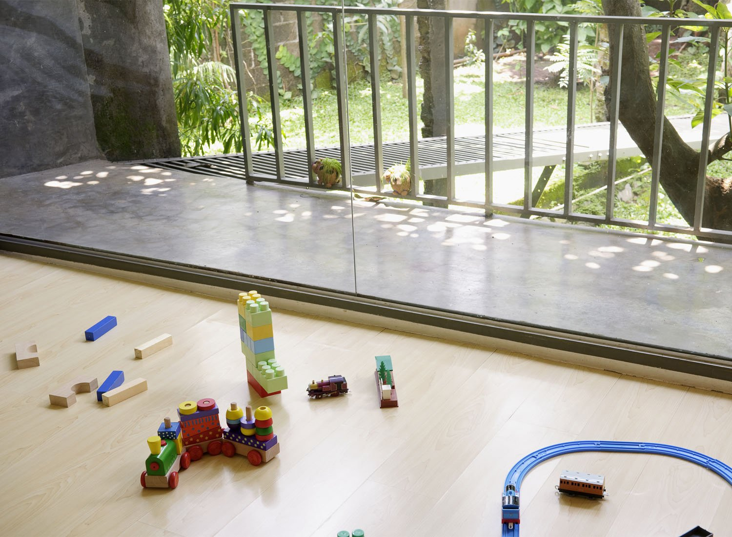 The family room upstairs is the heart of family live at the Wisnu residence. The view to the private backyard gives a sense of serenity, even if the kids' toys find their way across the floor.  Photo 20 of 26 in Humid City, Cool Home