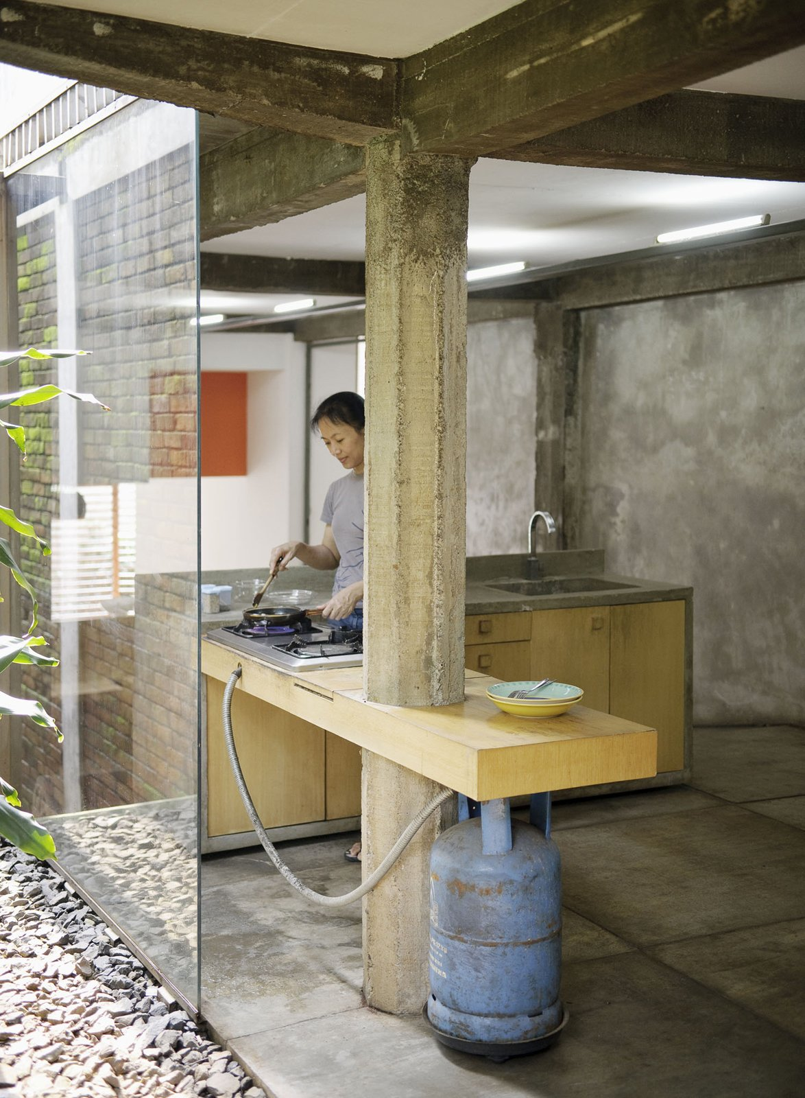 "Kitchen Here Sundari puts a bit of food together in the kitchen. A gas-fired grill and concrete countertop give the place a rough-hewn feel, and certainly evokes architect Ahmad Juhara's rally cray, ""Ad hocism is my religion.""  Photo 22 of 26 in Humid City, Cool Home"