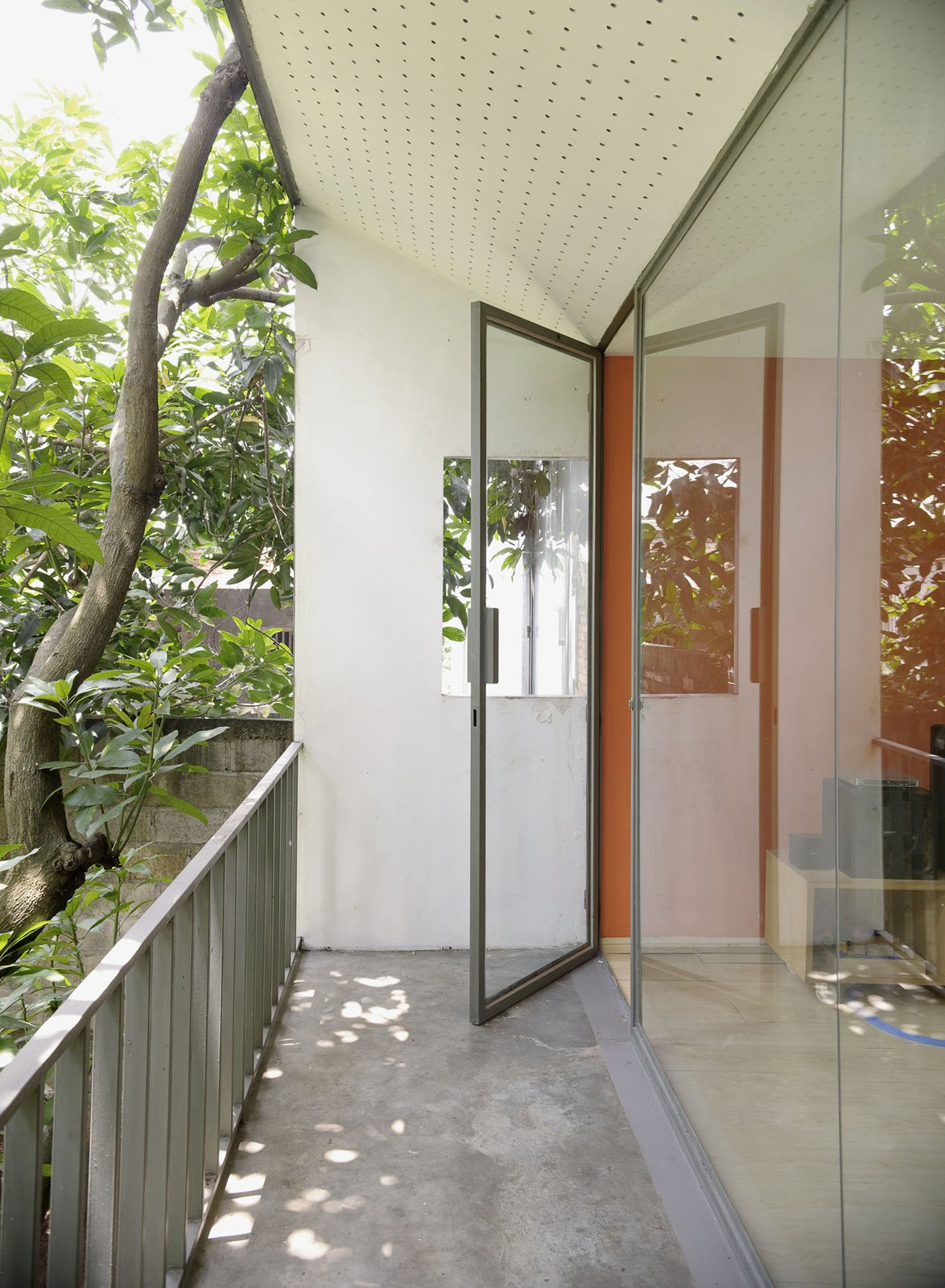Doors That orange accent is carried from a door downstairs to the family room upstairs and a glazed facade keeps things very bright indeed.  Photo 24 of 26 in Humid City, Cool Home