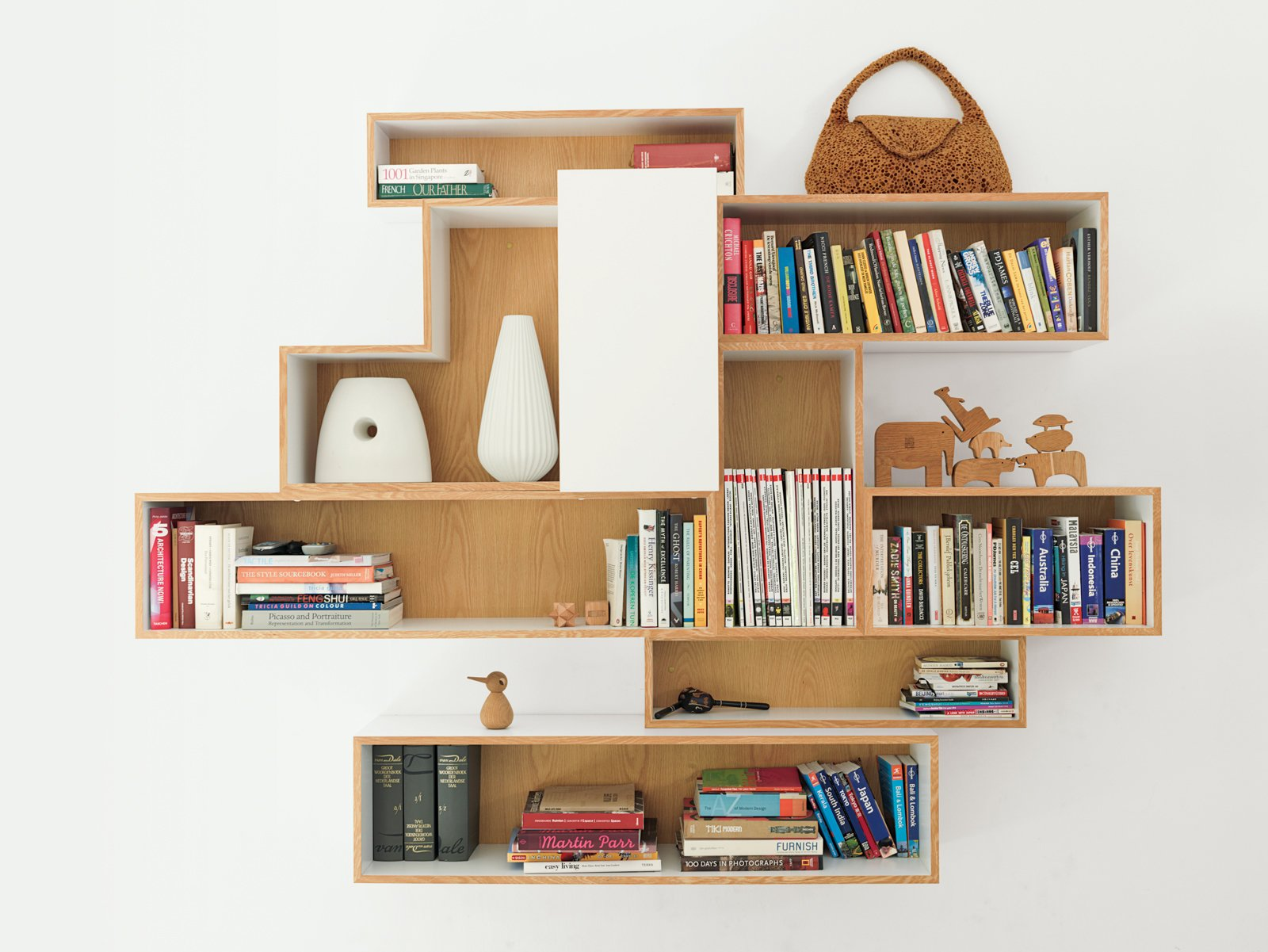The house lacked significant storage space when the family moved in, so De Waart designed bookcases to custom-fit their favorite display items.  Photo 6 of 11 in A Family Moves from Netherlands to Singapore