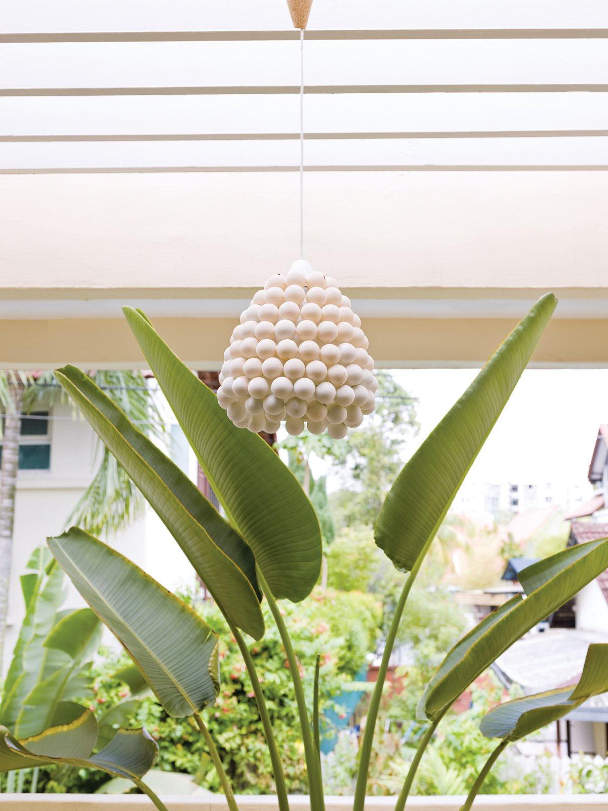 """One of the first things De Waart did when they moved in was to remove   all the curtains—–save those on the bedroom windows—–and change the lighting fixtures. """"A nice lamp can add so much extra to a room,"""" she says. De Waart favors organic shapes, like the Evolute by Matali Crasset for Danese Milano in the family room, Arco by the Castiglioni brothers for Flos in the living room, or the ping-pong-ball pendant light of her own design on one of the balconies.  Photo 10 of 11 in A Family Moves from Netherlands to Singapore"""