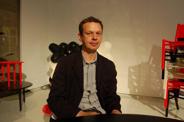 Designer Tom Dixon poses in his booth at the 2010 International Contemporary Furniture Fair.