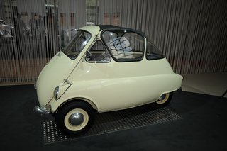 """A statement in economical, sensible and efficient transportation: the BMW Isetta. Its front-opening door and glass """"greenhouse"""" interior gave way to it being known as the """"bubble-car."""" This """"microcar"""" was meant for short-distance travel and stands at a minimal 7.5 ft long by 4.5 ft wide. Designed in Italy, it can accommodate two adults (and maybe a small child) comfortably."""