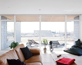 The living room receives ample light through the south-facing glass doors and floor-to-ceiling windows.