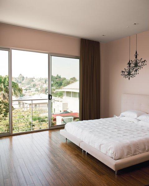 The Owenses' minimalist master bedroom features Blik wall decals of chandeliers.