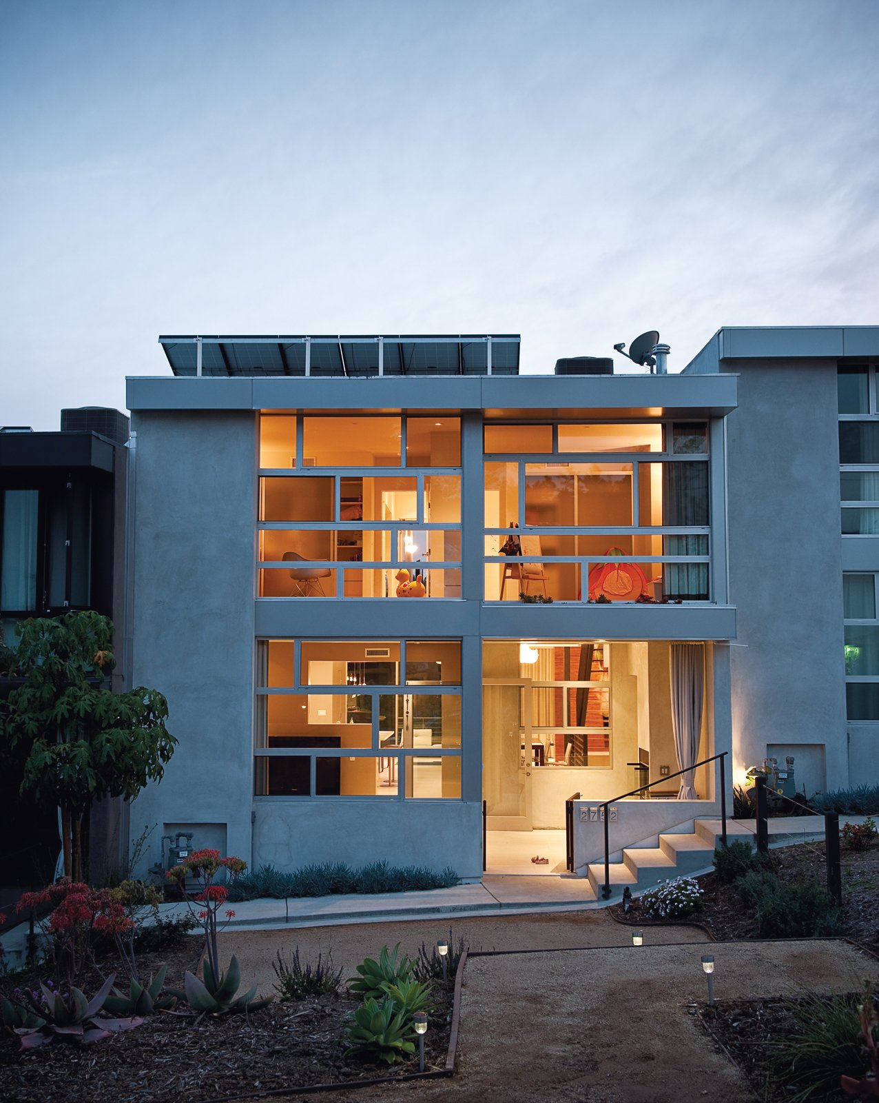 Architects Ana Henton and Greg Williams broke up the uniformity of the seven town homes by making a feature of the Jeldwin dual-glazed windows, laid horizontally here and vertically on the neighboring units.  Photo 15 of 15 in Lucky 7