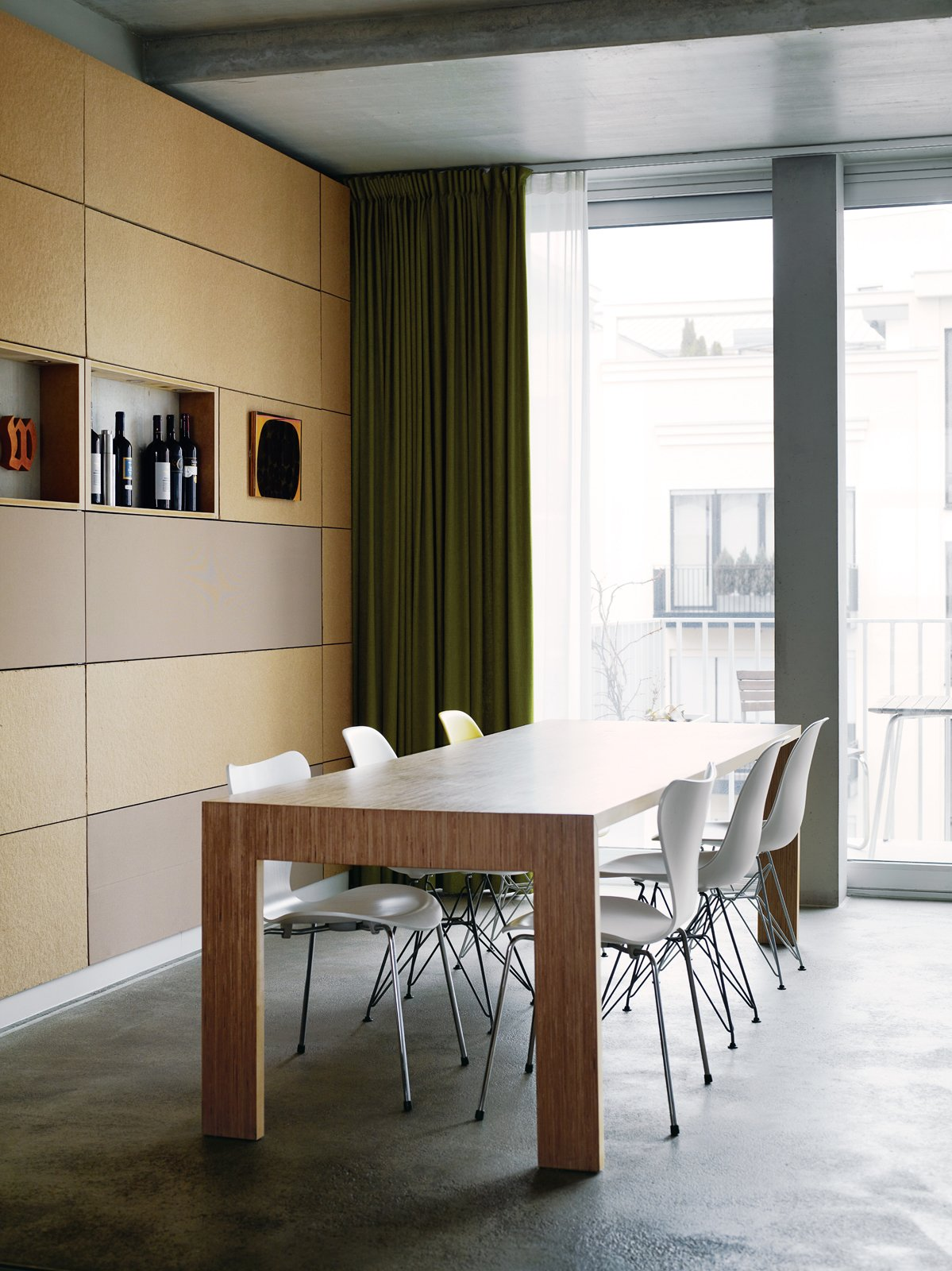 Next to the kitchen, Eames and Jacobsen chairs welcome dinner guests to the dining-room table. The back wall is covered in particleboard panels. Tagged: Dining Room, Concrete Floor, Table, and Chair.  Photo 1 of 16 in A Rational Approach