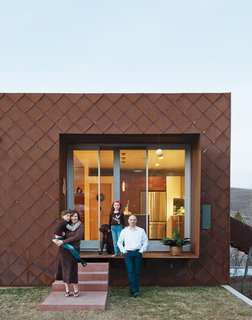 The house is clad with scales made of Cor-Ten steel that have weathered and rusted over time and create framed views into rooms like the kitchen.