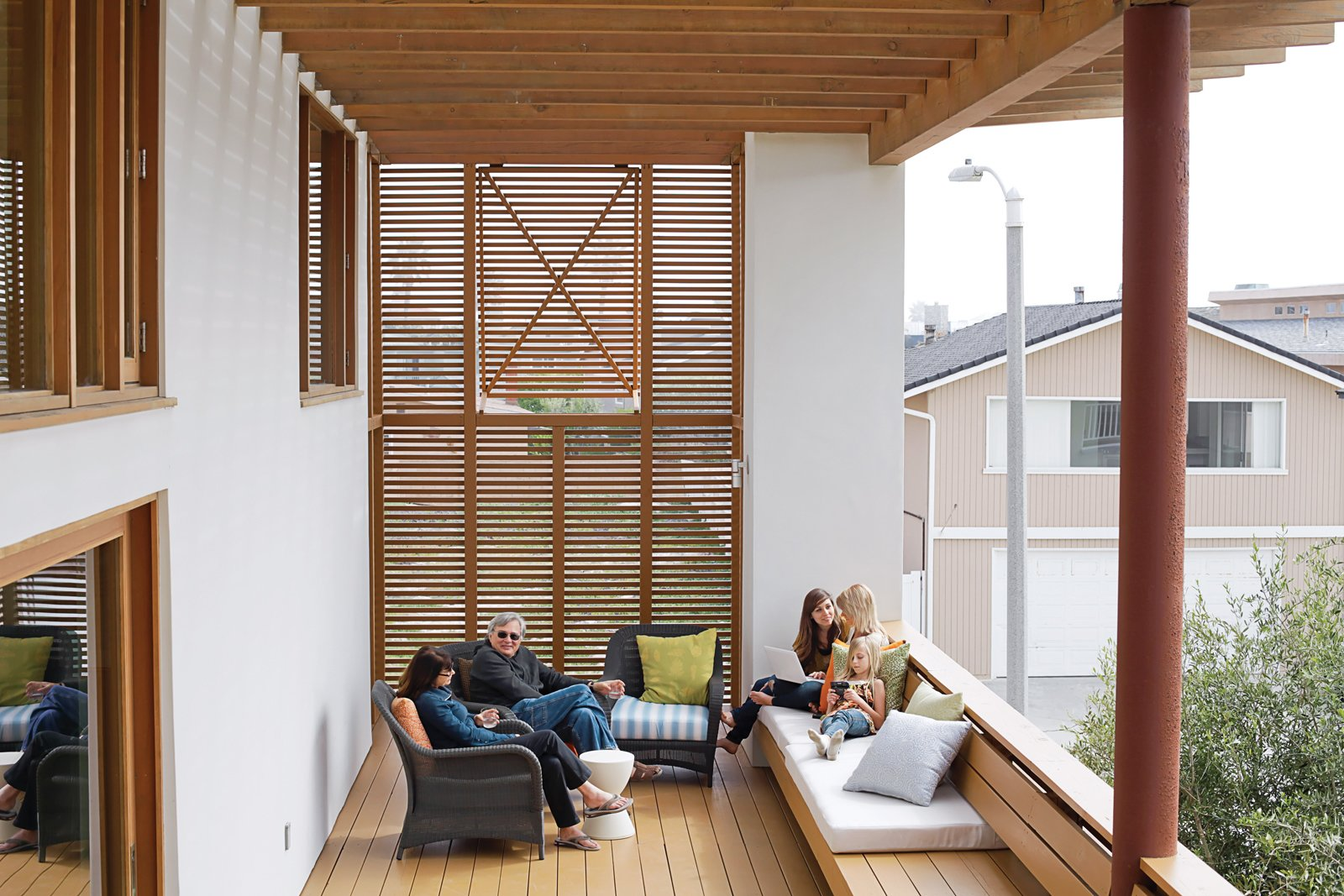 Outdoor, Small Patio, Porch, Deck, and Wood Patio, Porch, Deck Cedar louvers increase privacy and shade on the second-floor deck, where Carole and Duane relax with granddaughters Natalie and Allison and their friend Katherine.  Photos from Coast Docs