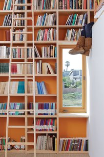 To make the most of 13-foot-high ceilings that help draw hot air out through second-floor windows and doors, designer Daniel Garness painted select walls with playful color and lined them with maple plywood bookcases. Library ladders (about $1,500 each from Alaco Ladder Company) provide access to reading material and a sleeping loft.