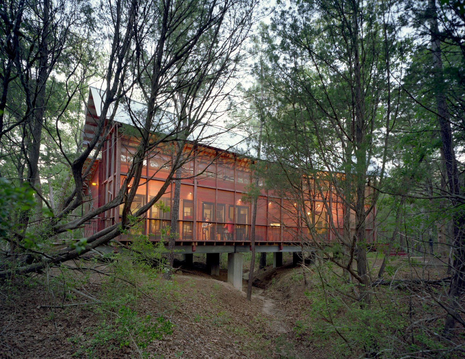 A screen porch runs the entire length of building, built over a dry creek bed on embedded concrete piers. The architect says he worked with the varying topography and native pines, turning the building 30 degrees at one point to accommodate the natural contours of the land.  Texas Bunkhouse by Erika Heet