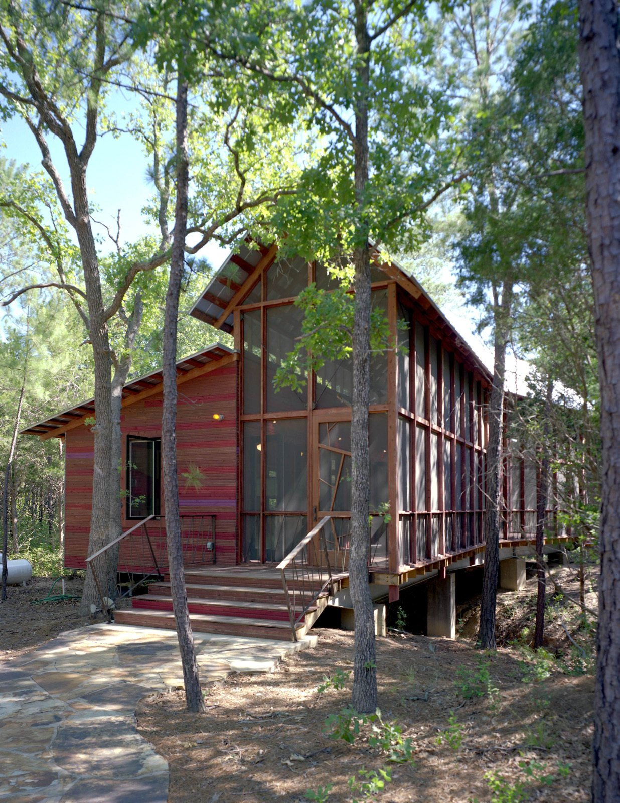 """A stone path leads from a gravel parking area to the entrance, fronted by a wide stair and small porch. """"Since we had to slot it in between so many trees with such vertical proportions, we decided our building would have vertical proportions,"""" says Panton. At left is the enclosed bunkroom, with the double-height screen porch at right.  Texas Bunkhouse by Erika Heet"""