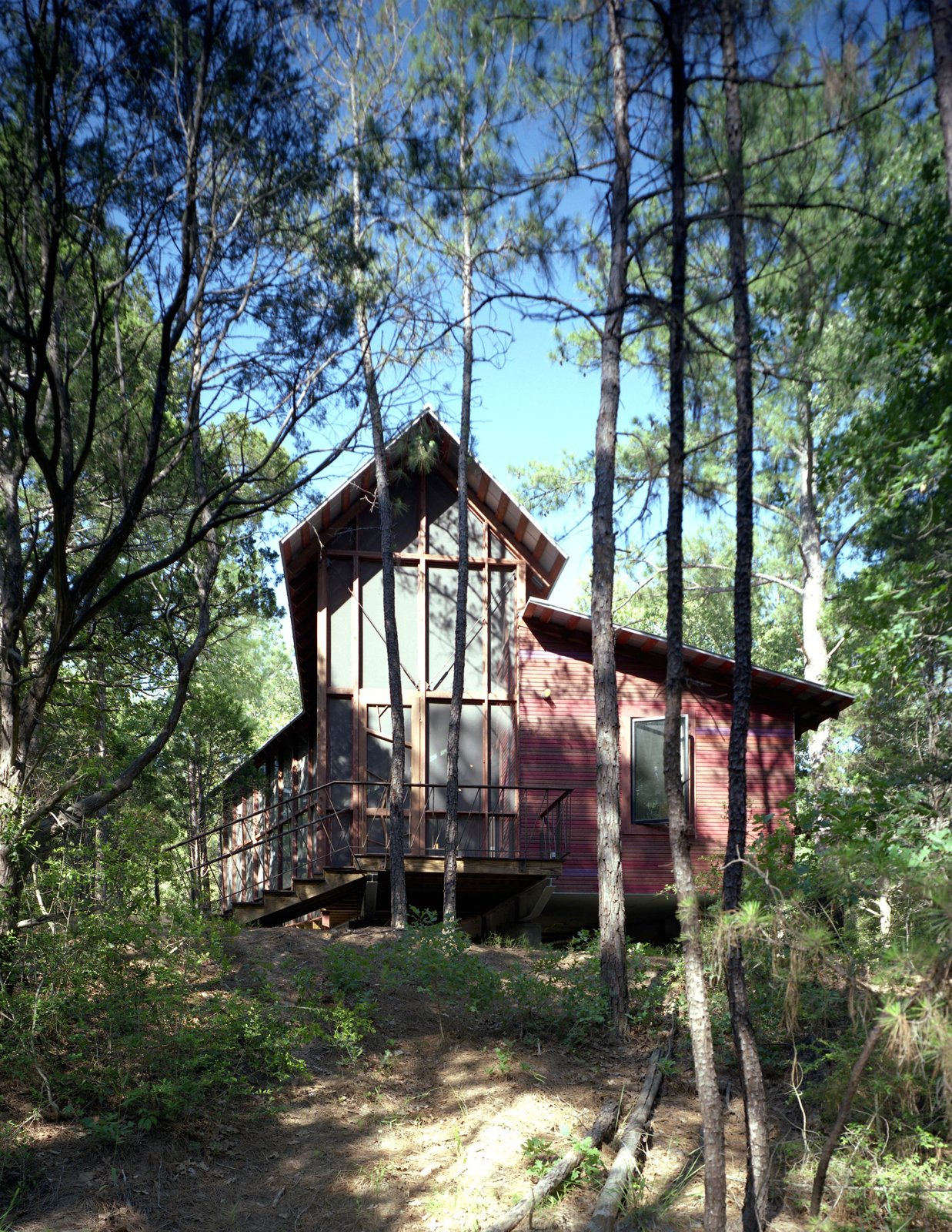 The opposite side of the bunkhouse, with the only enclosed bedroom, which leads to a small galley kitchen and two bathrooms, at right. This exit leads to a path to a nearby footbridge, swimming pool and outdoor bathhouse.  Texas Bunkhouse by Erika Heet