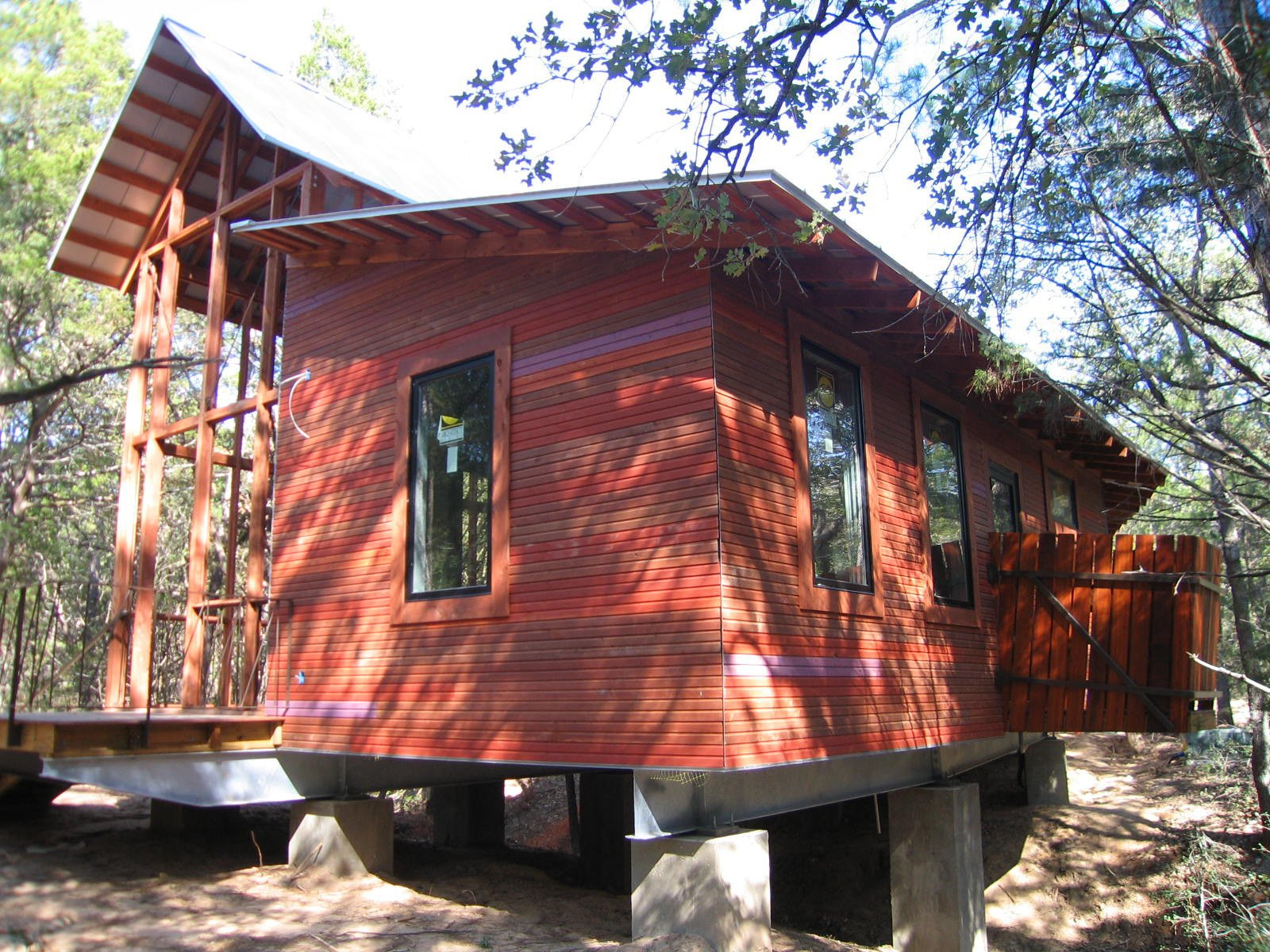 """The structure was built onto a concrete-and-steel base. At left is the porch, pre-screening; at right is a cantilevered outdoor shower off the bathroom. The exterior cladding is cedar, stained in four different colors then placed randomly """"for a different palette of colors, like a blend of bricks,"""" says Panton. """"The owner's favorite color is purple, so we added a purple board here and there.""""  Texas Bunkhouse by Erika Heet"""