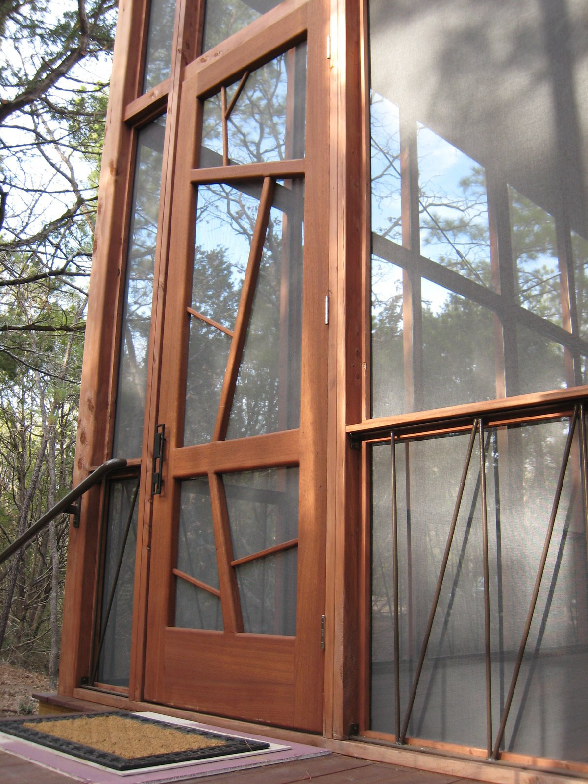 """The nine-by-three-foot mahogany entrance door is meant to evoke the surrounding trees. The iron handrails lining the base of the porch are a subtle architectural detail, as well as a support system to prevent the cabin from ever twisting or shifting """"like so many old Texas outbuildings,"""" says Panton.  Texas Bunkhouse by Erika Heet"""