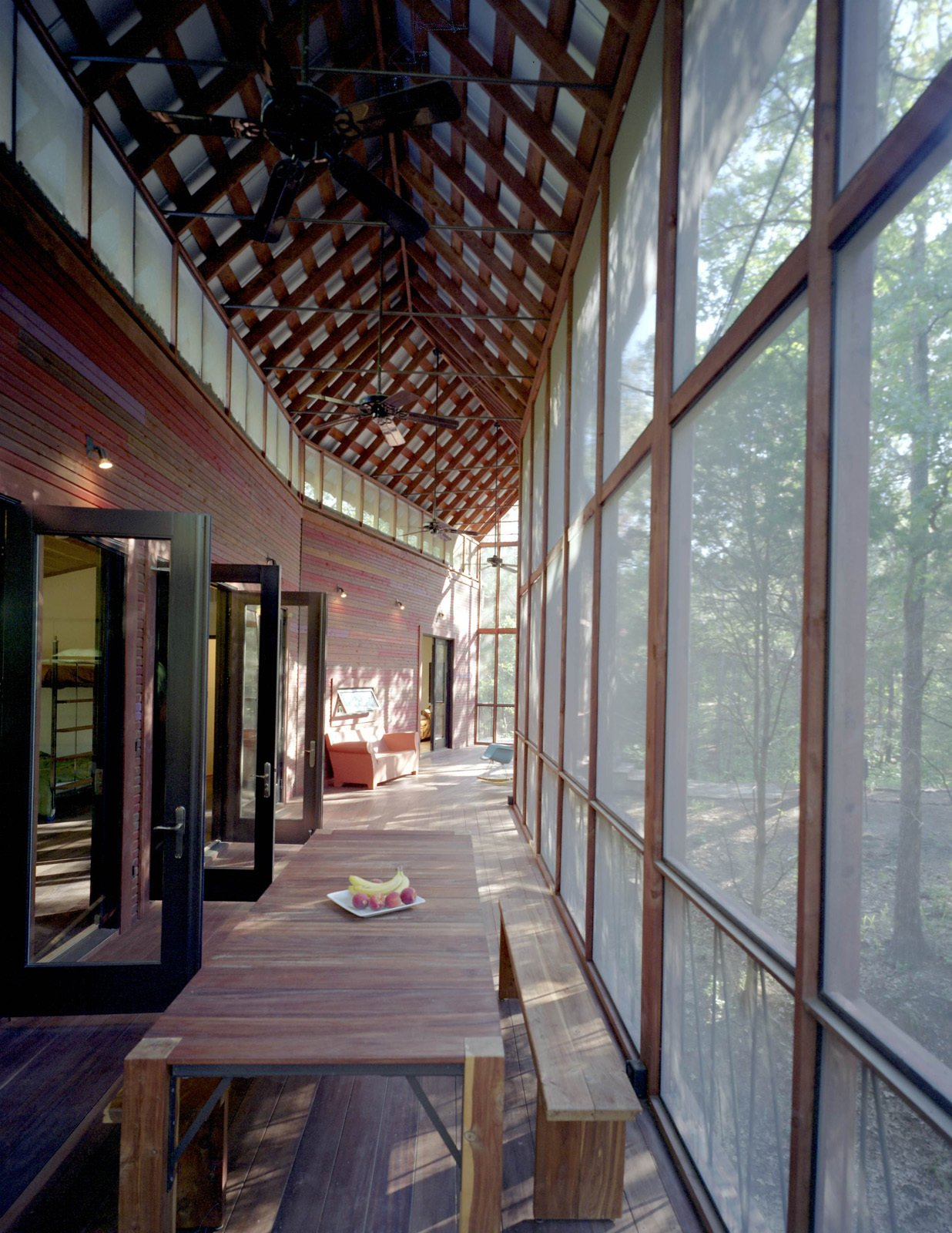Several sets of aluminum-and-glass French doors open from the bunkroom onto the screen porch. Panton and his team made the dining table and benches on-site; the tongue-and-groove benches and table legs are locally milled cedar, and the top is Brazilian Tigerwood.  Texas Bunkhouse by Erika Heet