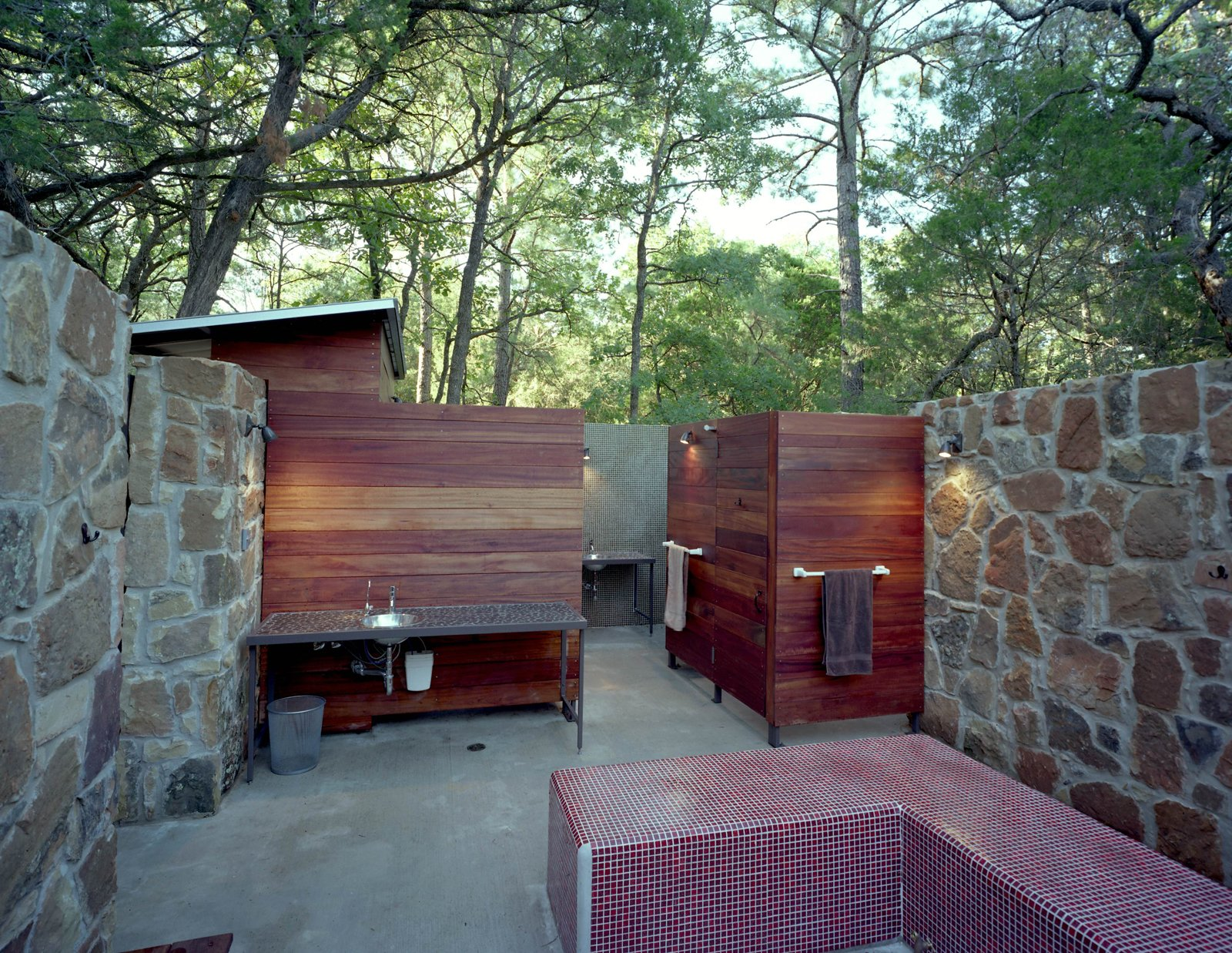 With its Brazilian Tigerwood enclosures, the outdoor bathhouse, which includes showers, sinks and dressing areas, references the nearby bunkhouse.  Texas Bunkhouse by Erika Heet